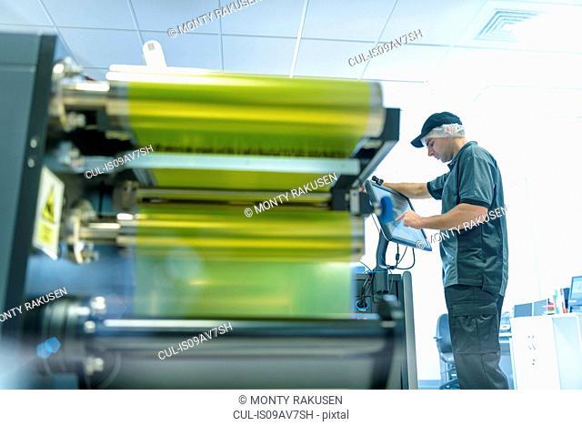Worker with ink jet printer in food packaging printing factory