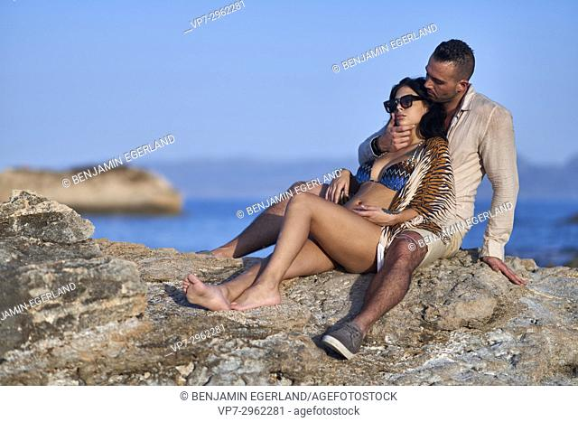 young couple together at Mediterranean beach. Greek ethnicity. In holiday destination Hersonissos, Crete, Greece