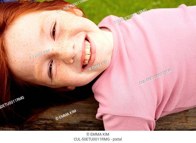 Smiling girl laying on wooden log