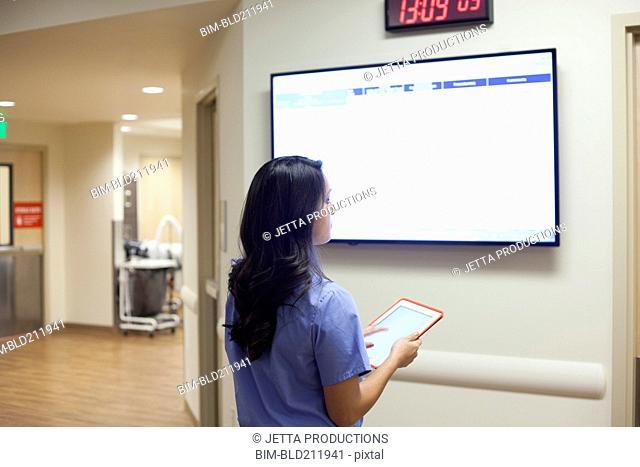 Nurse watching monitor in hospital corridor