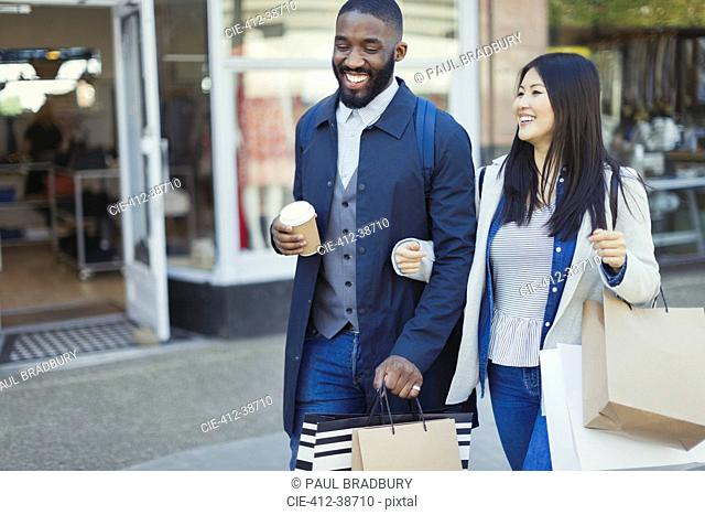 Smiling young couple walking arm in arm along storefront with coffee and shopping bags