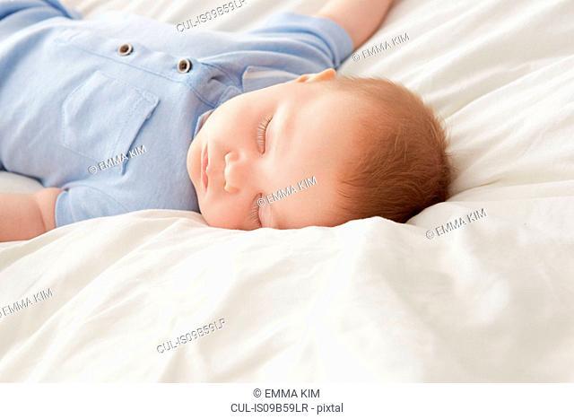 Baby boy lying on bed asleep