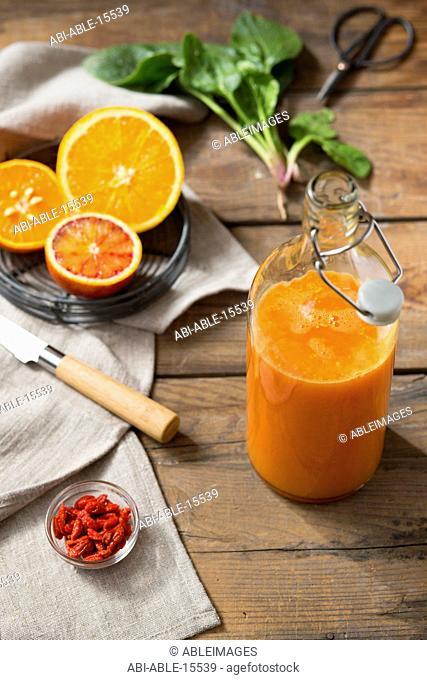 Juice, Oranges and Goji Berries on Wood Table