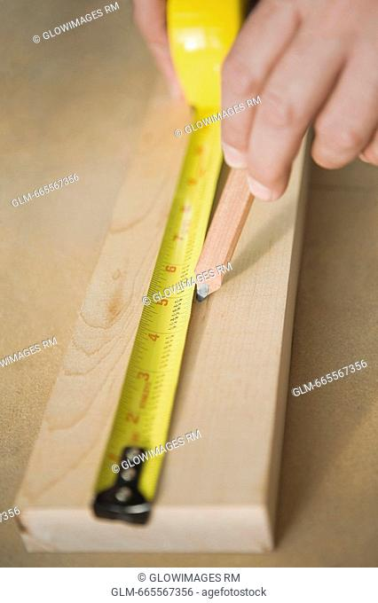 Close-up of a person's hands measuring a wooden plank