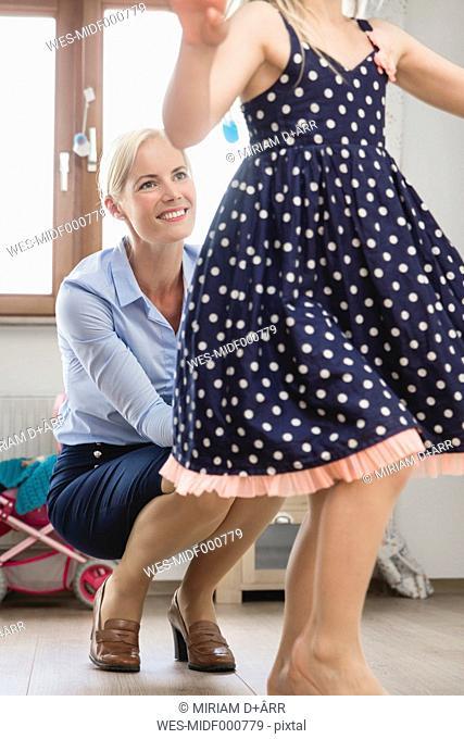 Businesswoman watching her little daughter dancing at children's room