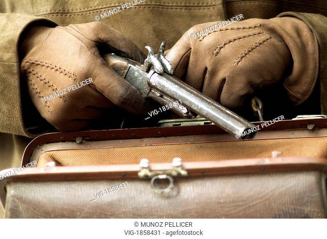 Hands with gloves hiding a gun in a leather handbag - SPAIN, 01/01/2006