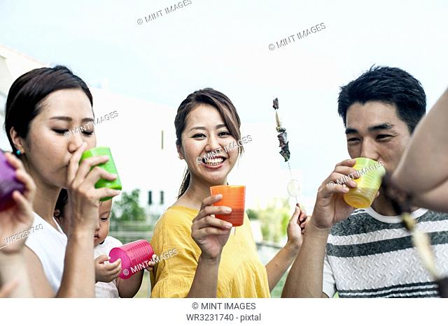 Group of Japanese men and women standing outdoors, drinking from plastic beakers