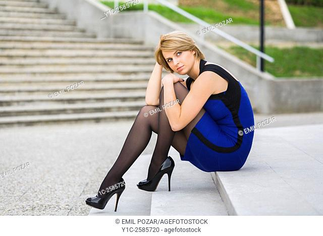 Fanciful attractive woman sitting on low staircase