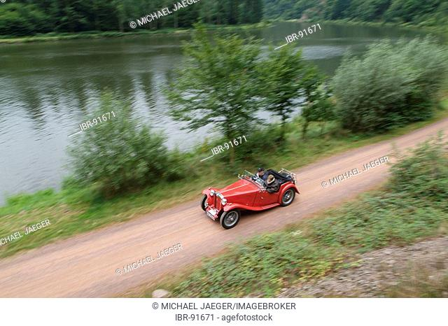 Red vintage car MG driving along a river