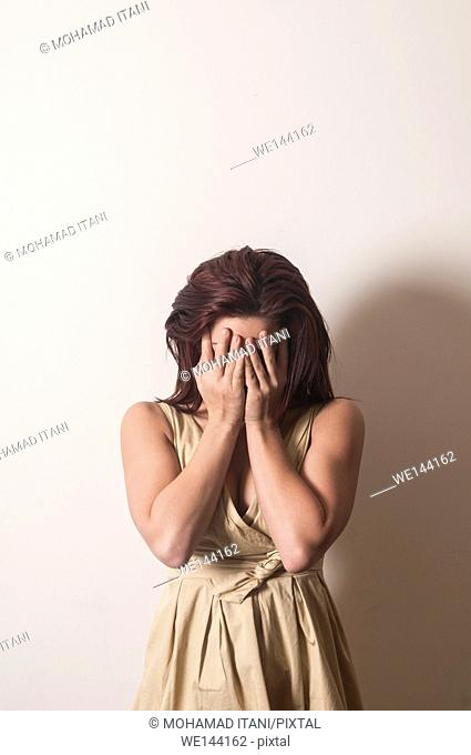 Scared woman hiding face with hands crying
