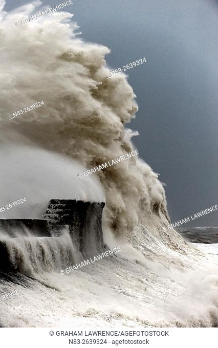 Huge waves crash against the harbour wall at Porthcawl, Bridgend, Wales, UK