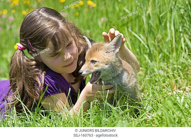 girl and young red fox on meadow