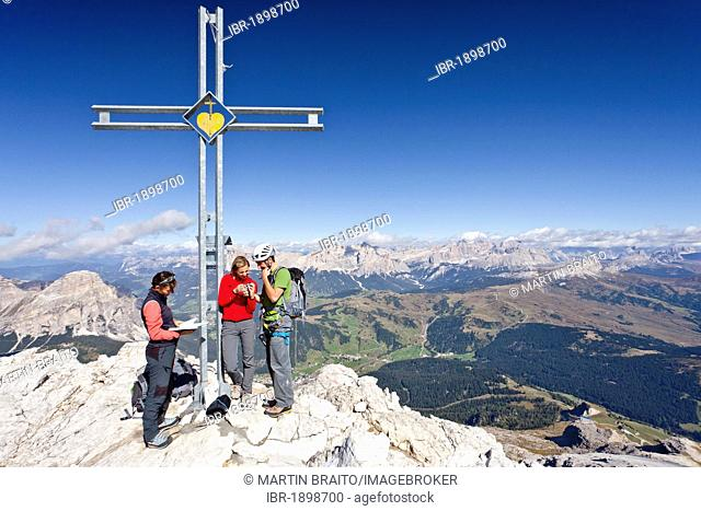 Climbers standing next to the summit cross, Boeseekofel fixed rope route, Dolomites, Fanes group and Heiligkreuzkofel group at the back, province of Trento
