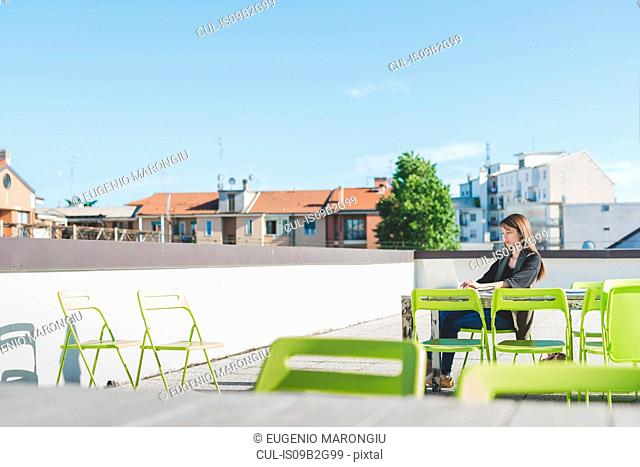 Young woman sitting on city roof terrace typing on laptop