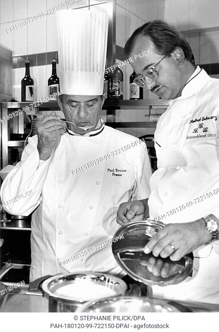 An archive photo from 16 February 1984 shows famous French chef Paul Bocuse cooking with his German colleague Manfred Schwarz (r) in Deidesheim, Germany