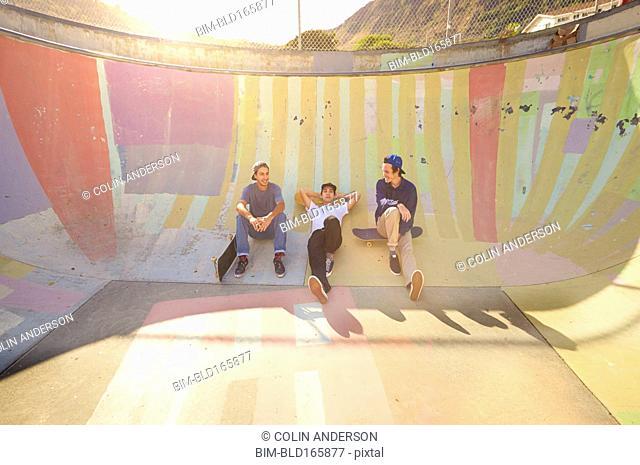 Men sitting on ramp in skate park