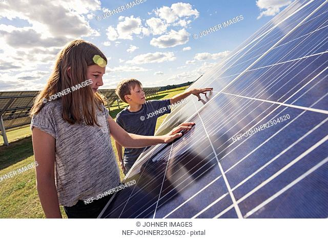 Boy and girl standing next to solar panels