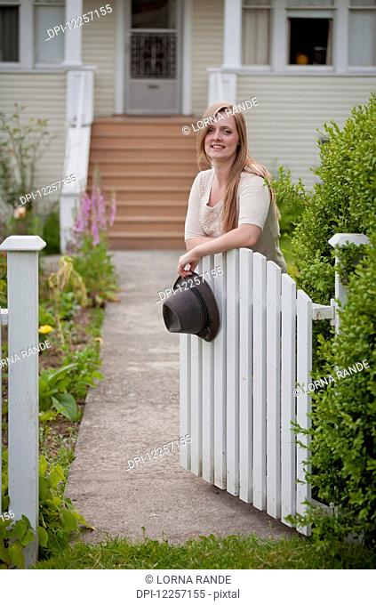 Woman standing at an open gate in front of a house; Vancouver, British Columbia, Canada