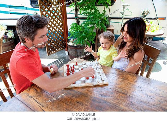 Parents and son playing chess