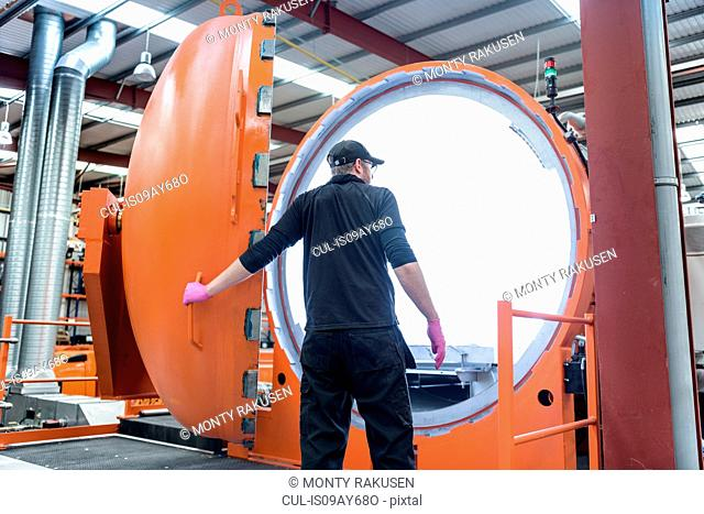 Engineer with autoclave in racing car factory