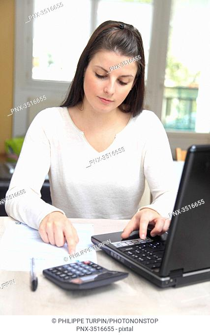 France, young woman at a computer filing her taxes online