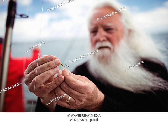 Fisherman adjusting fishing hook