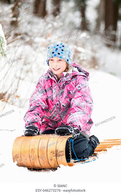 young girl in bright winter clothing having fun sledding down a snow covered hill in winter