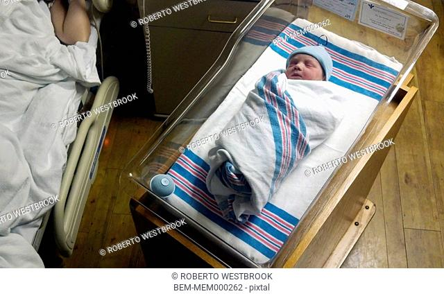 Caucasian newborn baby sleeping in bassinet