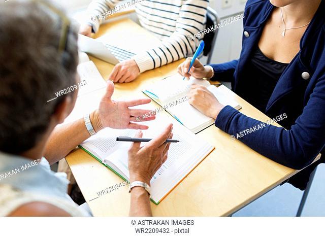 Mature professor teaching university students at desk in classroom