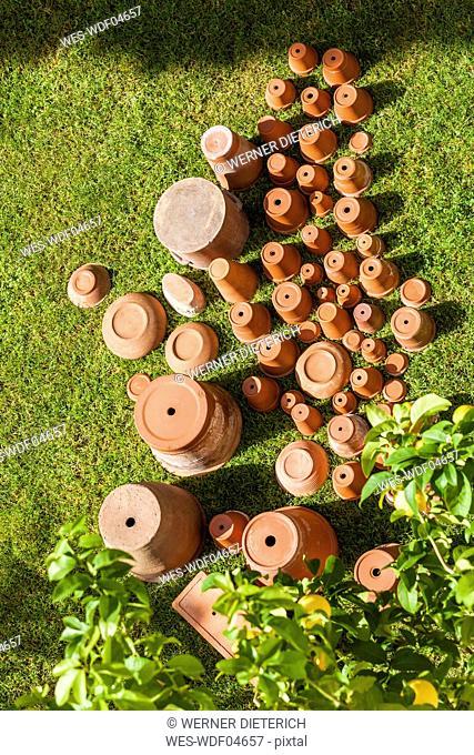 Empty flower pots standing upside down on grass