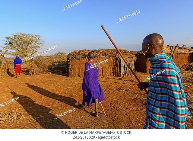 Maasai (Masai) men walking in a manyatta (plural manyattas) village or kraal. Satao Elerai Conservancy. Near Amboseli National Park. Kenya