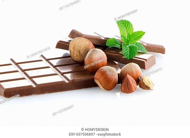 Chocolate Bar with hazelnuts and fresh mint on white background