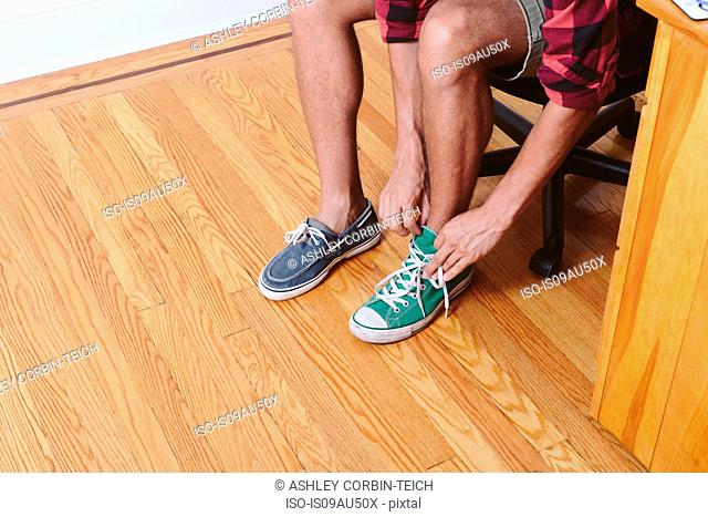 Young man sitting on chair trying on two different shoes, low section