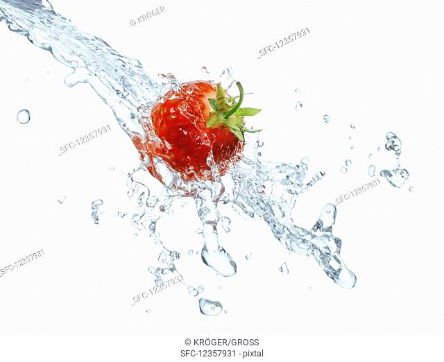 A strawberry with a splash of water