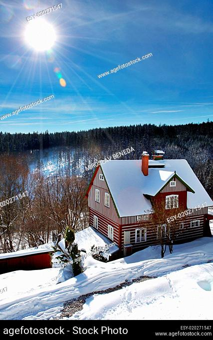 wooden old red cottage in winter with snow in Czech mountains