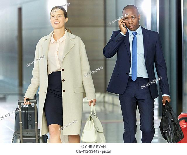 Business people walking with luggage in airport concourse