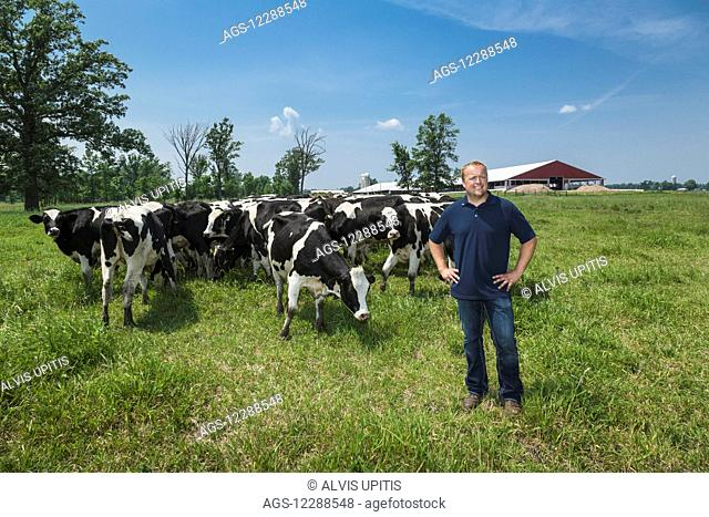 Dairy farmer with Holsteins in pasture; Grantsburg, Wisconsin, United States of America