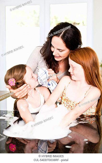 Mother wiping daughters face in kitchen
