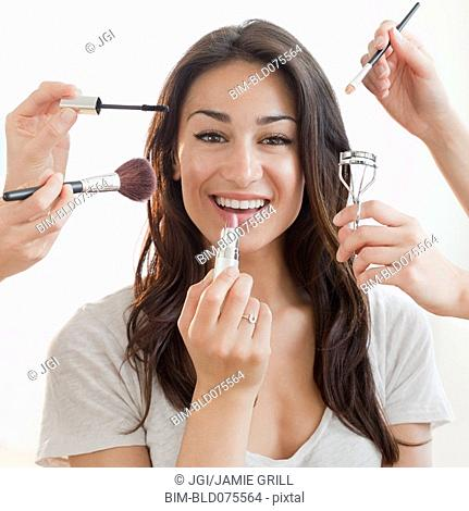 Hands applying makeup to Hispanic woman's face