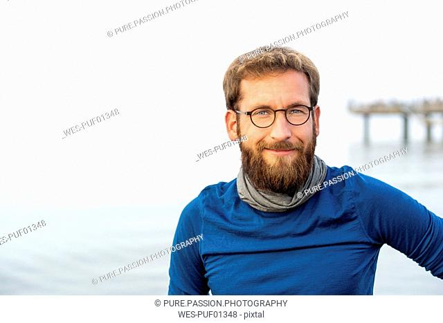 Germany, Rerik, portrait of bearded man in front of the sea wearing metal-rimmed spectacles