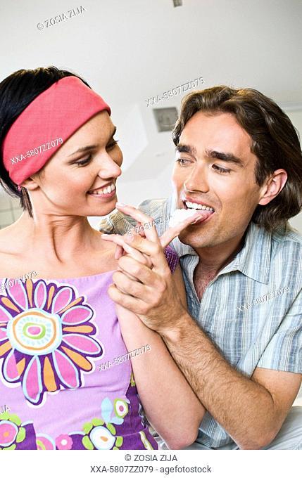 woman feeding man with cream