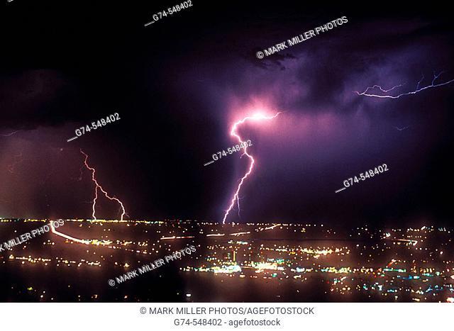 Lightning strikes at night over city lights