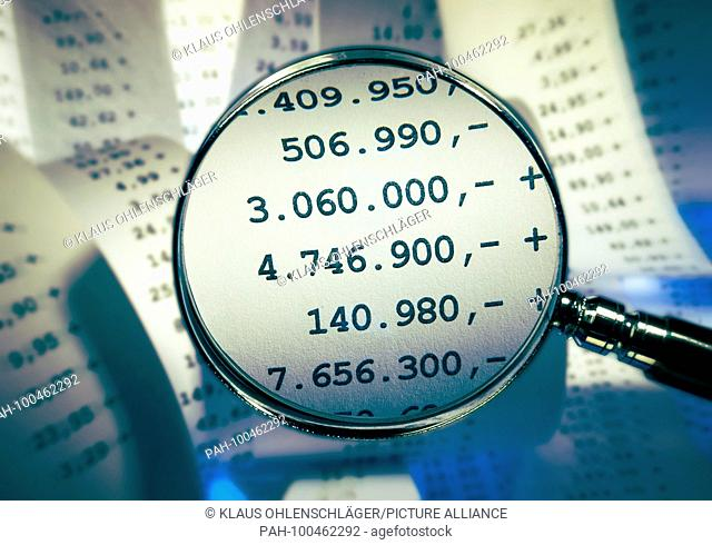 Magnifier focussing high sums in front of a background with receipts | usage worldwide