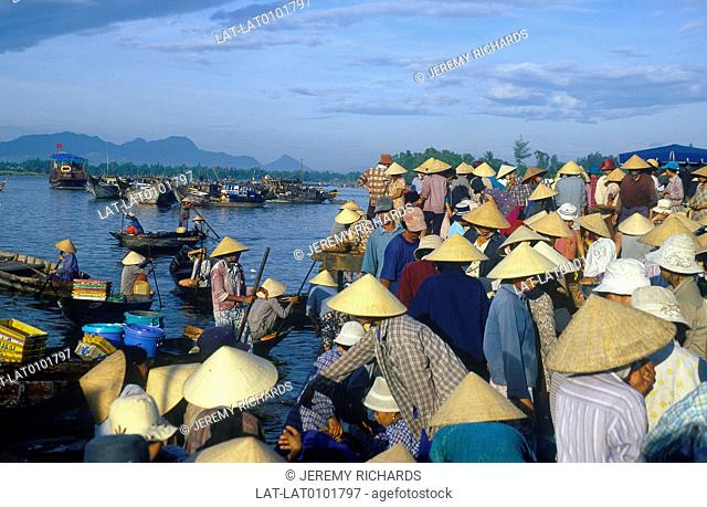 Riverside. Fish market. Crowd of people in hats on quayside. Houseboats,fishing boats