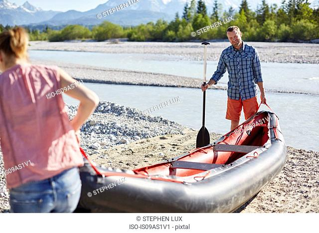 Couple carrying dinghy to water holding paddle