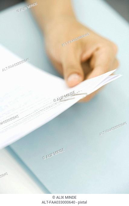 Person reading document, cropped view of hand