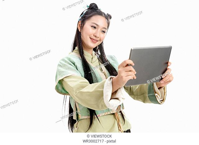 A woman in costume looking at a tablet computer