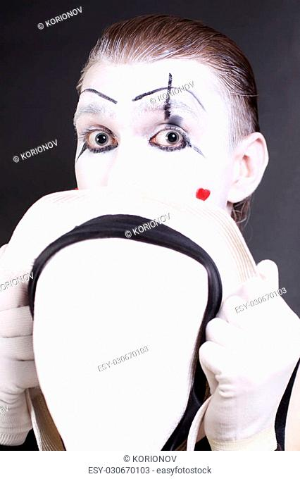 mime holding white hat