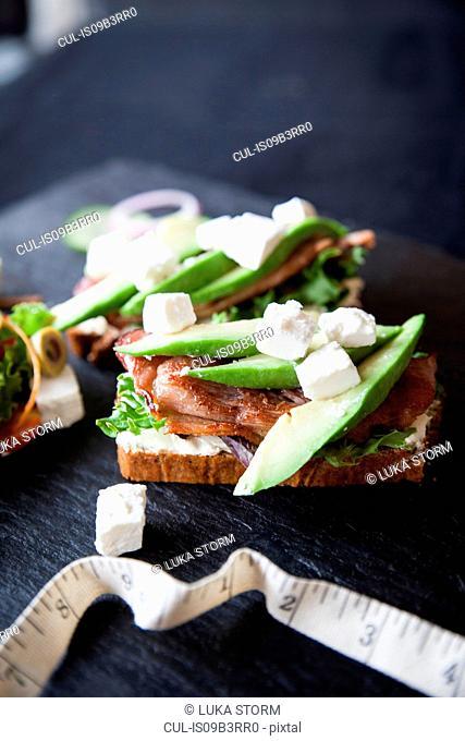 Meat, feta and avocado open sandwiches on slate