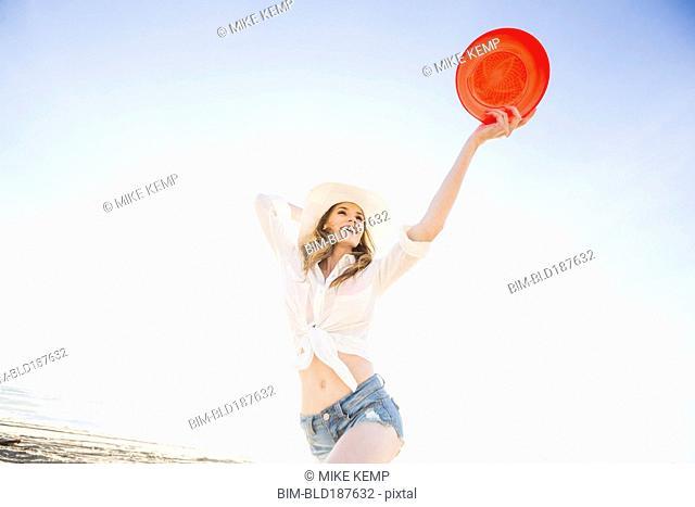 Caucasian woman holding plastic disc on beach